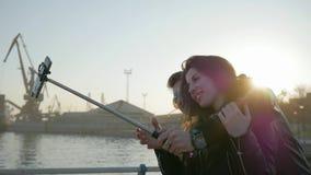 La gente joven es el abrazo fotografiado, artilugio en el palillo del selfie, foto del selfi de los pares felices, uno mismo-pali almacen de metraje de vídeo