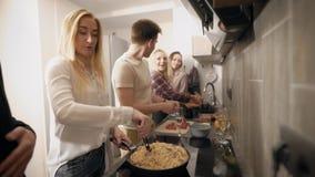 La gente joven está cocinando junta en cocina moderna, dos mujeres está lavando verduras, la otra muchacha está revolviendo la go almacen de video