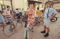 La gente joven feliz con viejo-moda monta en bicicleta la reunión en el festival popular de la ciudad Fotos de archivo