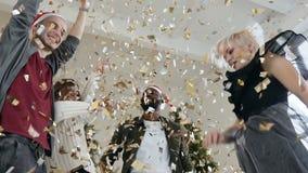 La gente joven feliz está bailando confeti del oro que lanza en el partido de la celebración Las muchachas y los individuos hermo metrajes