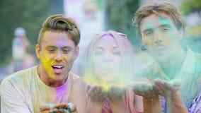 La gente joven feliz que sostiene el polvo coloreado en las manos, soplando teñe a la cámara almacen de video