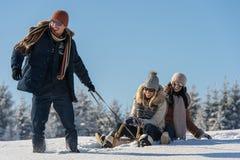 La gente joven goza del trineo soleado del día de invierno Imágenes de archivo libres de regalías