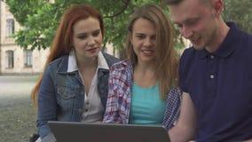 La gente joven mira algo en el ordenador portátil en campus almacen de metraje de vídeo