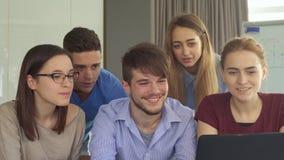 La gente joven muestra sus pulgares para arriba en la oficina