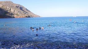 La gente joven nada y se divierte en el mar azul, Creta almacen de video