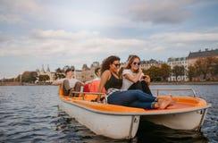 La gente joven que goza del barco monta en el lago Foto de archivo libre de regalías