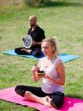 La gente joven que medita en yoga clasifica en verano en naturaleza Foto de archivo libre de regalías