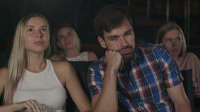 La gente joven que mira una película aburrida en el cine, un individuo está durmiendo metrajes