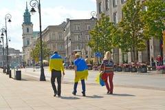 La gente joven que se ha envuelto para arriba en las banderas ucranianas Foto de archivo