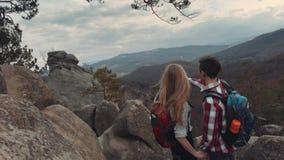 La gente joven que sube las montañas y que lleva a cabo sus manos, en la cima de la roca un hombre señala en algo, muchacha almacen de metraje de vídeo