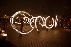 La gente joven realiza un espectáculo del fuego en la noche Imagen de archivo libre de regalías