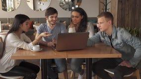 La gente joven señala sus índices en la pantalla del ordenador portátil almacen de metraje de vídeo
