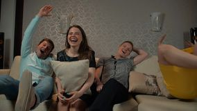 La gente joven se cae abajo en el sofá para ver la TV almacen de video