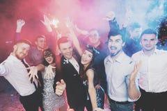 La gente joven se divierte en un partido del ` s del Año Nuevo Alrededor de ellos confeti de las moscas Foto de archivo