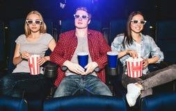 La gente joven se está sentando en sillas en cine Llevan los vidrios para las películas de observación El individuo tiene taza de Imagenes de archivo
