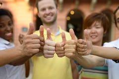 La gente joven sonriente que da los pulgares sube la muestra Imagenes de archivo