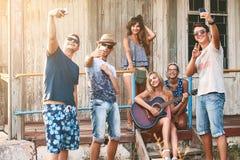 La gente joven toma el selfie con sus smartphones mientras que cuelga hacia fuera con los amigos en la cabina de madera del veran Imagenes de archivo