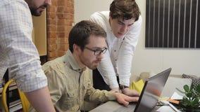 La gente joven trabaja junta y discute su puesta en marcha del negocio creativa que mira en el monitor del ordenador portátil Hom almacen de video