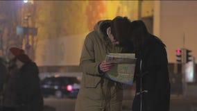 La gente joven viaja al extranjero, perdido en la megalópoli, buscando manera correcta en mapa de la ciudad almacen de video