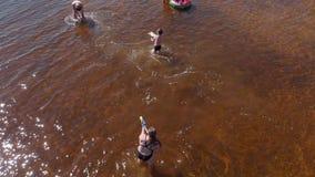 La gente juega en el agua por el río Verano metrajes