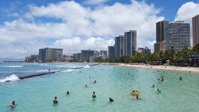 La gente juega en el agua protegida y cuelga hacia fuera en la playa Fotos de archivo