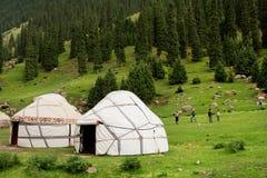 La gente juega a los juegos al aire libre cerca de las casas Yurts de los granjeros del asiático en montañas asiáticas centrales Imagen de archivo