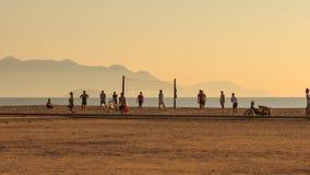 la gente juega a voleibol en la playa contra las colinas del mar en la salida del sol almacen de metraje de vídeo