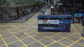 la gente 4K che aspetta in via occupata di Hong Kong dell'intersezione con il tram di traffico video d archivio