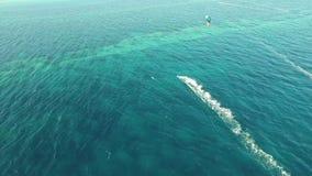 La gente kiteboarding en el océano azul claro de la turquesa riega en día de verano ventoso en sorprender paisaje marino aéreo de almacen de video
