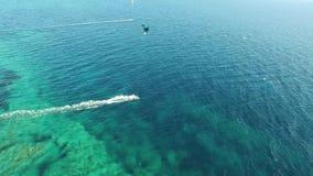 La gente kitesurfing en el océano azul claro de la turquesa riega en día de verano ventoso en aturdir panorama aéreo del paisaje  almacen de metraje de vídeo