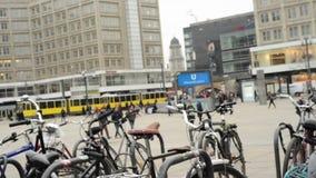 La gente, la cabina di funivia ed il treno trafficano al distretto Mitte di Berlino a Alexanderplatz