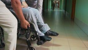 La gente lleva al hombre discapacitado en la silla de ruedas - ambiente inaccesible metrajes