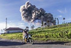 La gente local del pueblo que pasa por la tierra de cultivo como la ceniza del volcán pasa a ALTO en el cielo cuando el Mt Bromo  Fotografía de archivo libre de regalías