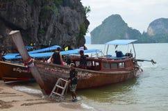 La gente local prepara el turista y los barcos de pesca para navegar Barcos en la orilla en la bahía en el fondo de montañas verd foto de archivo