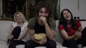 La gente mangia il popcorn e guarda la manifestazione di TV divertente di spettacolo e la trova molto divertente stock footage