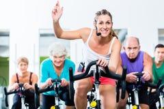 La gente mayor en el gimnasio que hace girar en aptitud bike Imagen de archivo libre de regalías