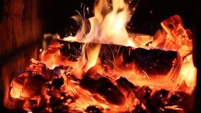 La gente mescola i carboni brucianti di un ferro di fuoco in un primo piano della fornace stock footage