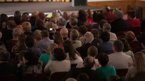 La gente messa in un pubblico e nell'applauso archivi video