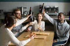 La gente milenaria diversa que cuelga hacia fuera junta la cerveza de consumición come imagen de archivo