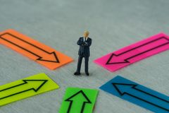 La gente miniatura calcola l'uomo d'affari che sta al centro dell'AR Immagine Stock
