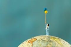 La gente miniatura con la giovane donna calcola lo standi dei palloni della tenuta Fotografia Stock