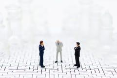 La gente miniatura, hombres de negocios se coloca en los lados opuestos del juego de ajedrez, partido separado, ventaja, uso como fotos de archivo libres de regalías