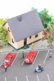La gente miniatura, la casa de ciudad y una calle muy transitada modelan fotografía de archivo