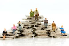 La gente miniatura, los viejos pares figura sentarse encima de monedas de la pila usando como planificación de la jubilación del  foto de archivo libre de regalías