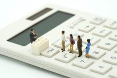 La gente miniatura paga la TASSA di reddito annuo della coda l'anno sul calcolatore usando come il concetto di affari del fondo e fotografia stock libera da diritti
