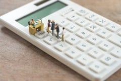 La gente miniatura paga la TASSA di reddito annuo della coda l'anno sul calcolatore usando come il concetto e finanza di affari d immagine stock