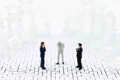 La gente miniatura, uomini d'affari sta dai lati opposti del gioco di scacchi, il partito separato, il beneficio, uso come concor fotografie stock libere da diritti
