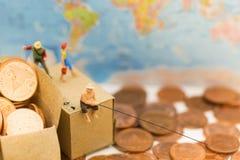 La gente miniatura, gente utiliza la caña de pescar para tomar el dinero de las monedas del piso y de la pila del descenso en la  Fotografía de archivo libre de regalías