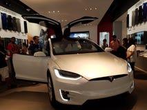 La gente mira el coche modelo de x dentro de la tienda de Tesla Fotos de archivo
