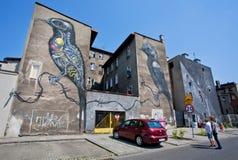 La gente mira el edificio exterior con la pintada de dos pájaros Fotografía de archivo libre de regalías